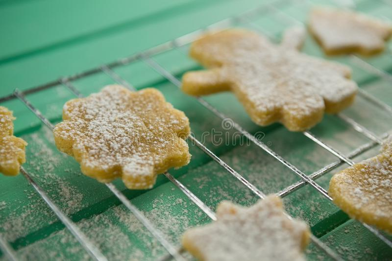 Close up of powdered sugar on cookies over cooling rack stock images
