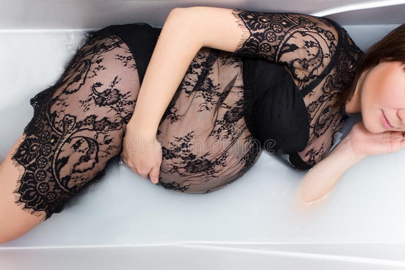 Close up of pregnant woman in lace dress lying in bath with milk stock image