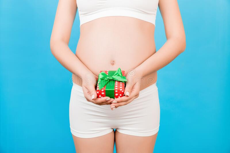 Close up of pregnant woman in white underwear holding a gift box at blue background. Childbirth expecting. Copy space.  royalty free stock photos