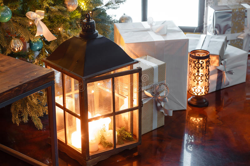 Close up of presents under the Christmas tree and candle in a lamp royalty free stock images