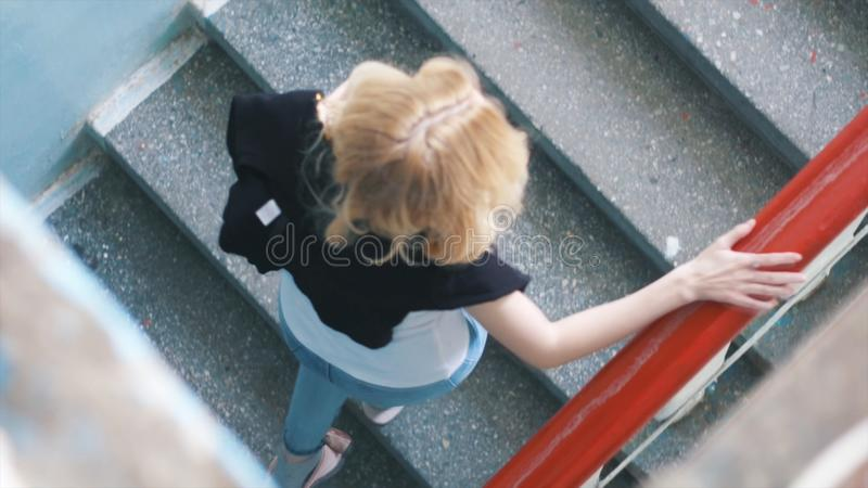 Close-up of pretty blond woman in white t-shirt, jeans and black jumper climbing the stairs in th entrance. Action stock image