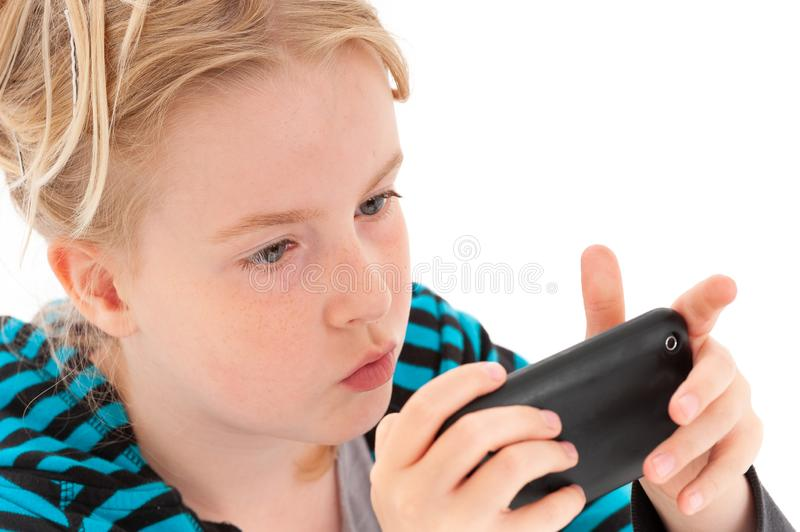 Close up of pretty blonde young girl staring intently at a smartphone. Isolated on a white studio background stock photos