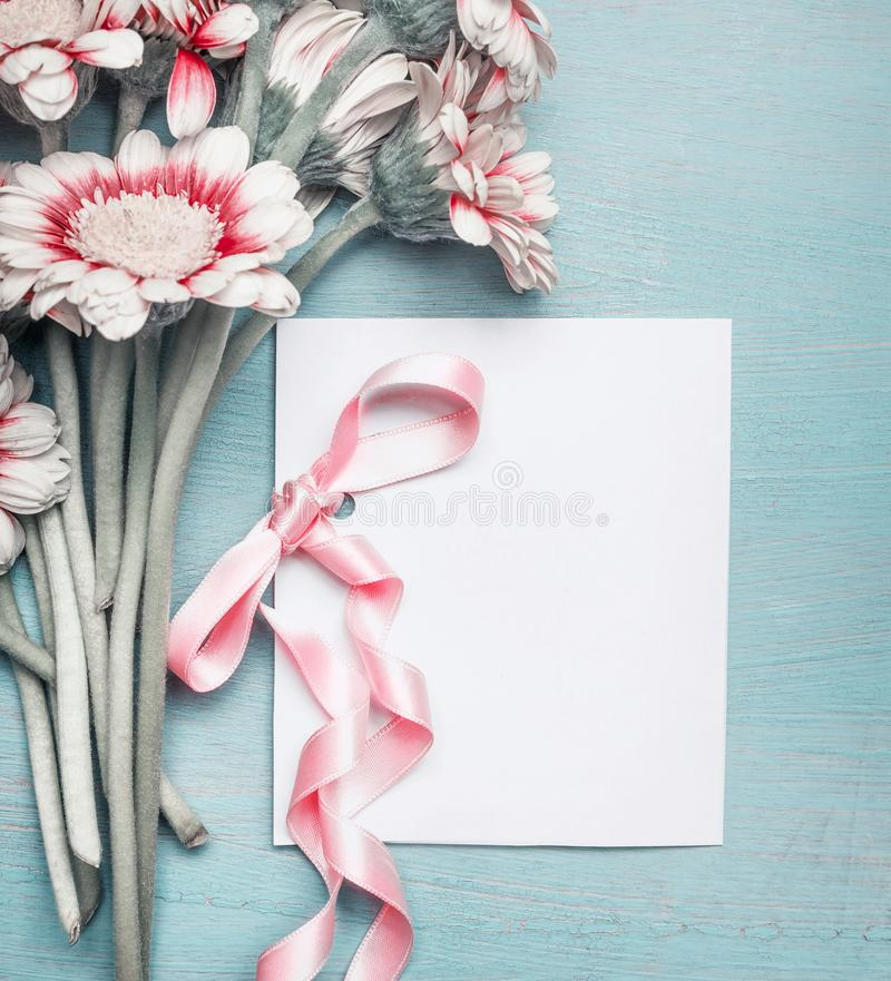 Close up of pretty flowers on turquoise blue shabby chic background and mock up of greeting card with pink ribbon. For Mothers day, wedding, Birthday or happy stock photos