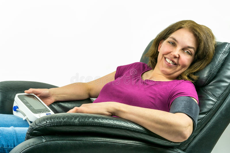 Close up of Pretty middle-age woman sitting in black leather recliner armchair. Checking blood pressure using portable blood press stock photo