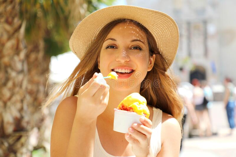 Close up of pretty tourist girl eating traditional gelato italian ice cream in Sirmione, Italy stock image