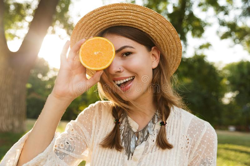 Close up of pretty young girl in summer hat spending time at the park, royalty free stock images