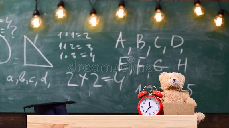 Close up of primary school classroom. Classroom with chalkboard on background. Childish desk with alarm clock and teddy stock image