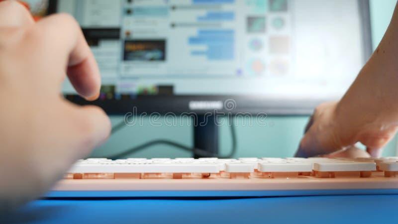 Close-up Primeira pessoa vista M?os f?meas que datilografam em mensagens cor-de-rosa de um teclado em redes sociais, contra o fun imagens de stock