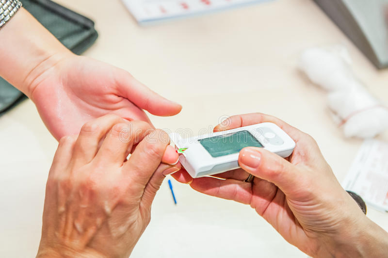 Close up process of mobile diabetes testing for sugar level. Normal blood sugar level. Doctor takes blood for test. Medical proces. S, modern healthcare concept royalty free stock photo