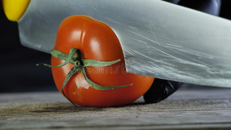 Close-up process of red pepper tomato, chef in black gloves slices tomato rings royalty free stock image