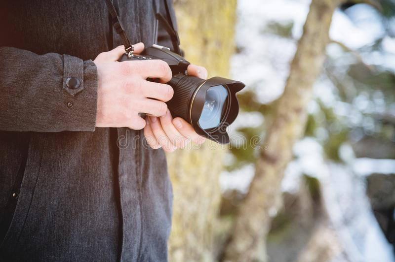 Close-up professional digital mirror camera in male hands in the winter forest. Photo travel concept stock photos