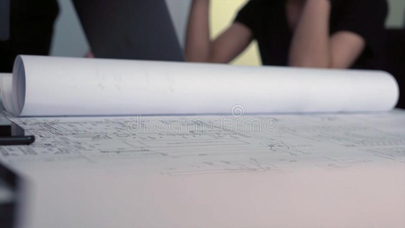 Close-up professional drawings of new project. Stock. Hands of professional engineers parsing project drawings indicate royalty free stock photography