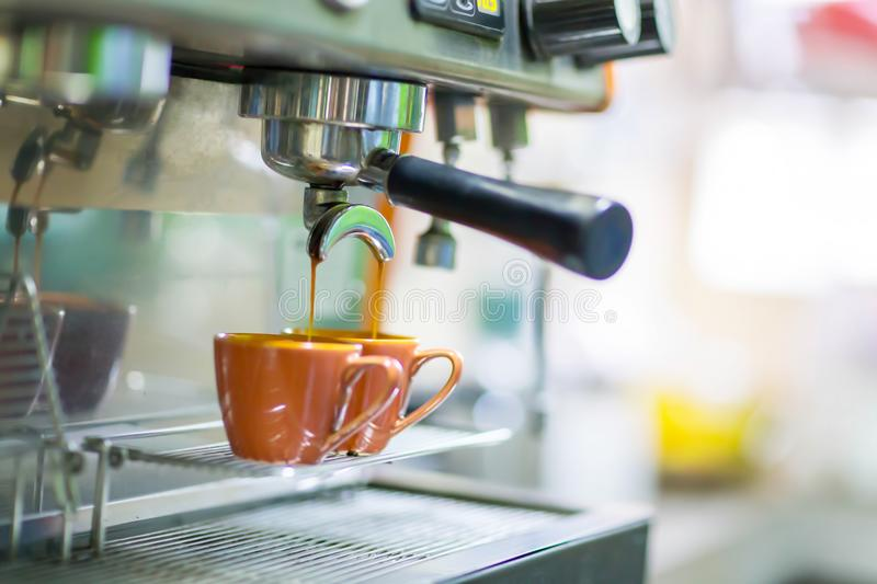 Close up professional espresso machine make coffee pouring into cup. royalty free stock photography