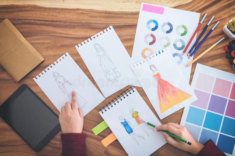 Close up of professional Fashion designer working and drawing sk stock image