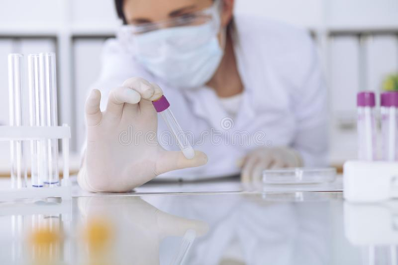 Close-up of professional female scientist in protective eyeglasses making experiment with reagents in laboratory. Close-up of professional female scientist in stock photo