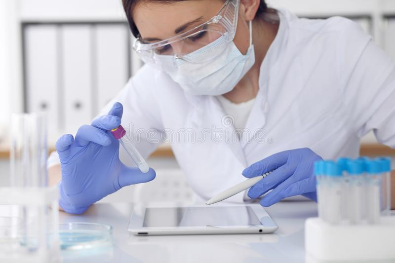 Close-up of professional female scientist in protective eyeglasses making experiment with reagents in laboratory. Close-up of professional female scientist in stock image