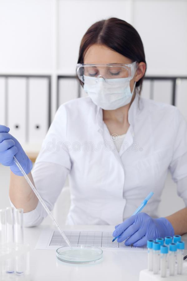 Close-up of professional female scientist in protective eyeglasses making experiment with reagents in laboratory. Close-up of professional female scientist in stock images