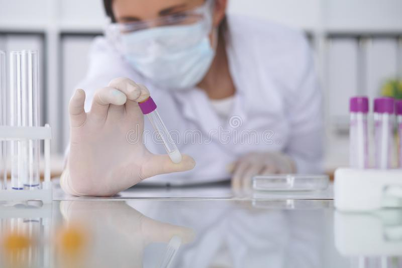 Close-up of professional female scientist in protective eyeglasses making experiment with reagents in laboratory. Close-up of professional female scientist in stock photos