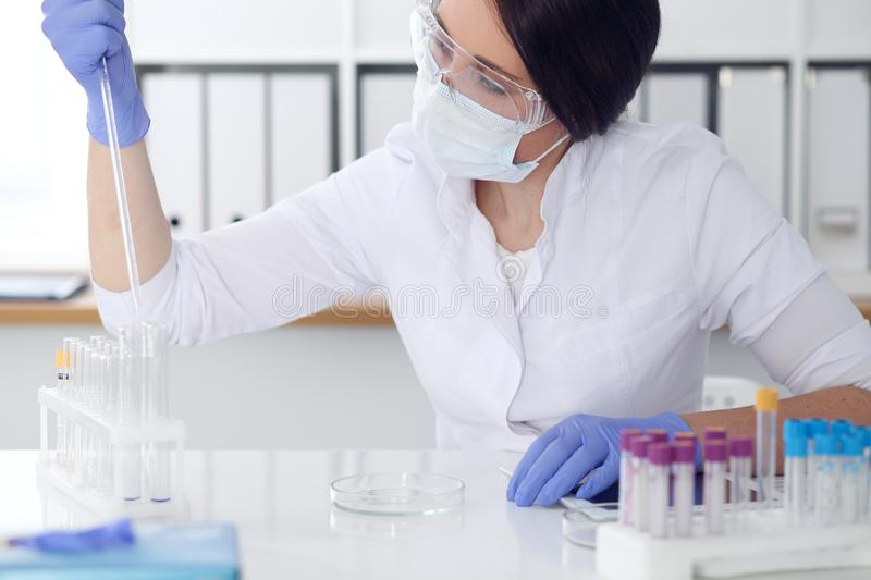Close-up of professional female scientist in protective eyeglasses making experiment with reagents in laboratory. Close-up of professional female scientist in stock photography