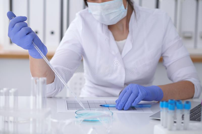 Close-up of professional female scientist in protective eyeglasses making experiment with reagents in laboratory. Close-up of professional female scientist in royalty free stock photo