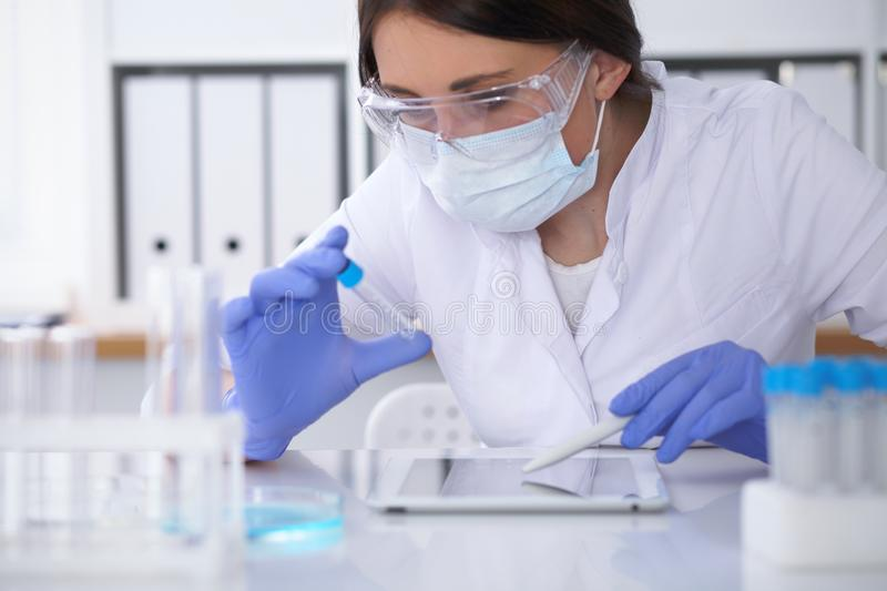 Close-up of professional female scientist in protective eyeglasses making experiment with reagents in laboratory. Close-up of professional female scientist in royalty free stock photos