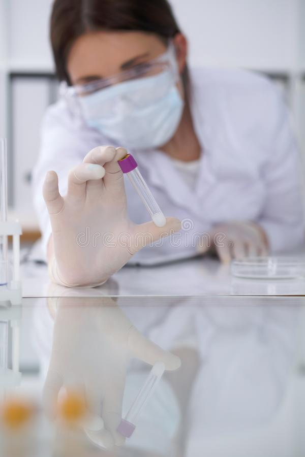 Close-up of professional female scientist in protective eyeglasses making experiment with reagents in laboratory. Close-up of professional female scientist in royalty free stock images