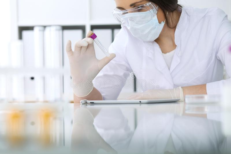 Close-up of professional female scientist in protective eyeglasses making experiment with reagents in laboratory. Close-up of professional female scientist in royalty free stock photography