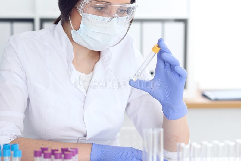 Close-up of professional female scientist in protective eyeglasses making experiment with reagents in laboratory. Close-up of professional female scientist in royalty free stock image