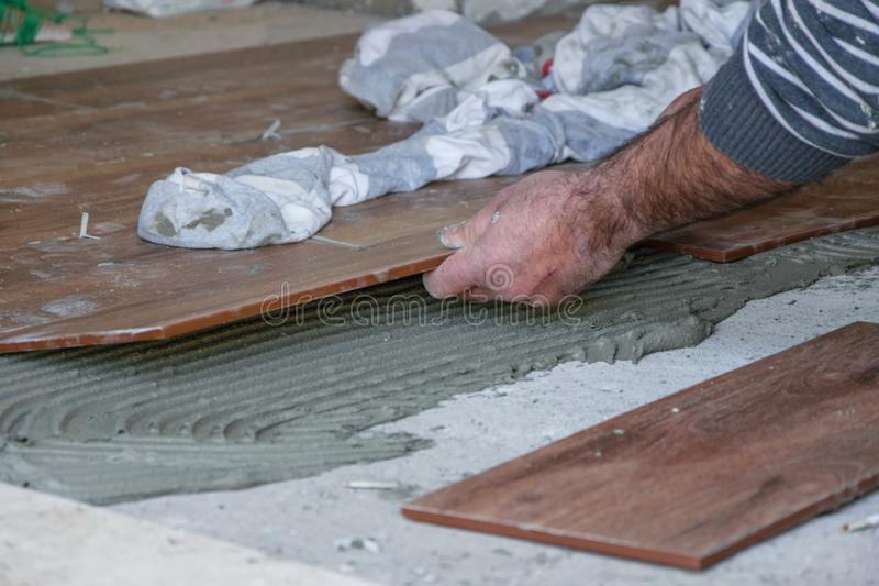 Close Up of professional mason worker indoor - laying tiles on floor at construction site royalty free stock photos