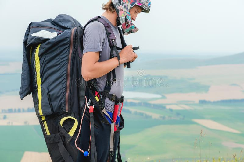 Close-up of a professional paraglider with a cocoon on his shoulders buttons helmet looks to the side. Paraglider sport royalty free stock photos