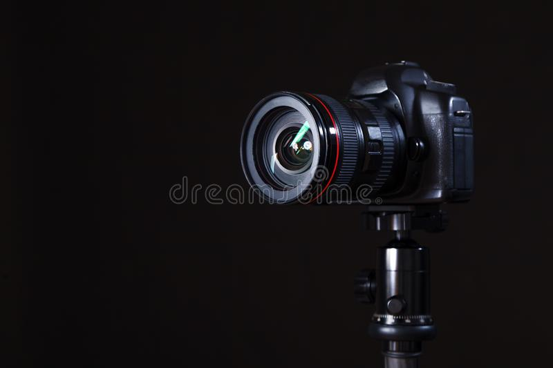 Close-up of professional photocamera in studio on black background. Concept of photoshoot royalty free stock image