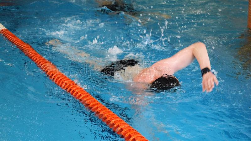 Close up for professional swimmer in slow mothion while swimming race in indoor pool. Athlete training, swimming the. Crawl in the pool royalty free stock photo