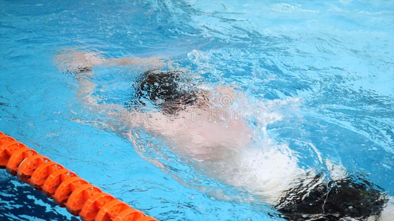 Close up for professional swimmer in slow mothion while swimming race in indoor pool. Athlete training, swimming the. Crawl in the pool stock photography