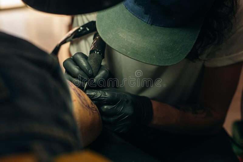 Close up of professional tattooer artist doing picture on hand of man by machine black ink from a jar. Tattoo art on body royalty free stock photography