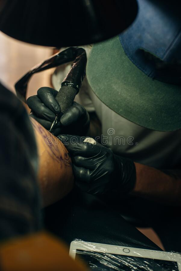 Close up of professional tattooer artist doing picture on hand of man by machine black ink from a jar. Tattoo art on body royalty free stock image