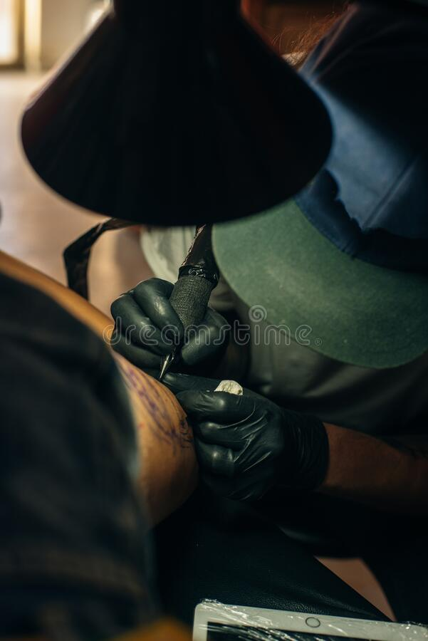 Close up of professional tattooer artist doing picture on hand of man by machine black ink from a jar. Tattoo art on body stock photos