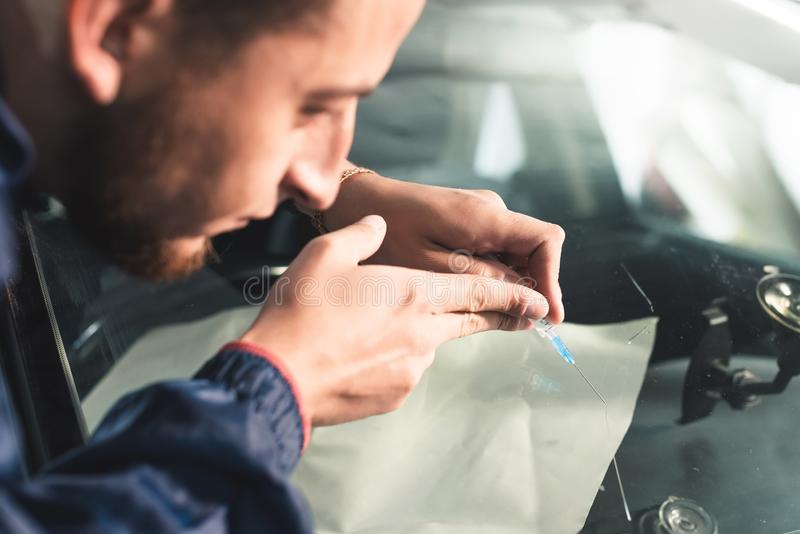 Close-up of a professional windshield repairman fills a crack in the glass with a special polymer through a syringe. Elimination of cracks and chips on stock photography
