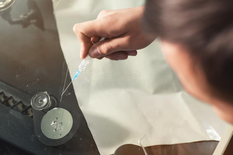 Close-up of a professional windshield repairman fills a crack in the glass with a special polymer through a syringe. Elimination of cracks and chips on royalty free stock photos