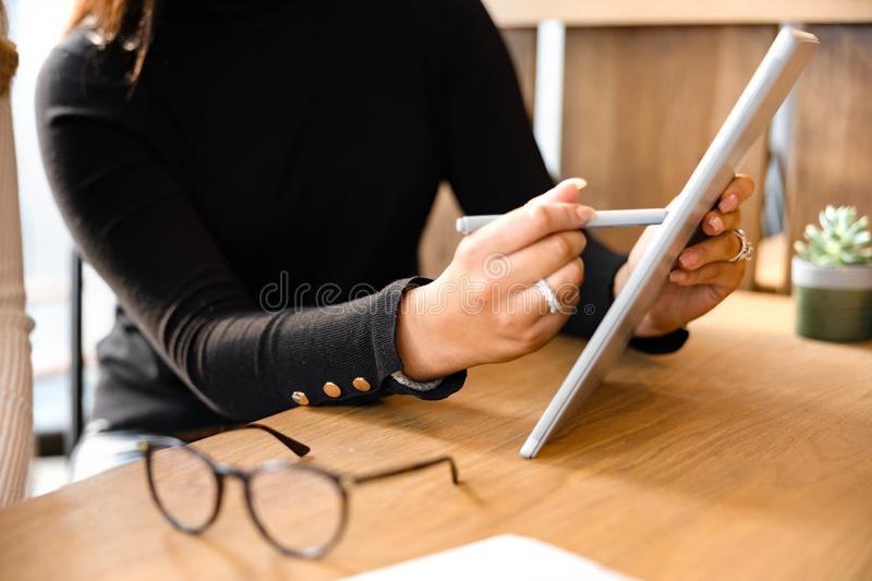 Close-up of Professionals Discussing Over Digital Tablet At Cafe stock photo