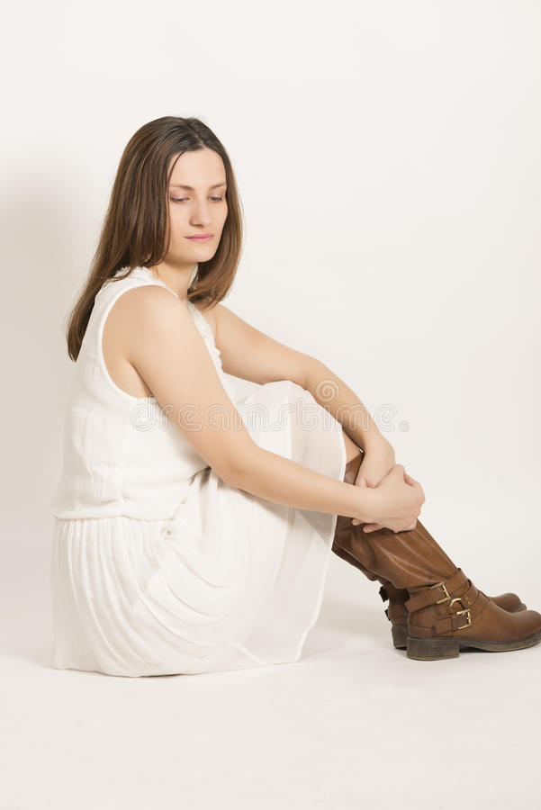 Close up profile of beautiful woaman. Sad beautiful woman in white dress and brown boots, studio shot on white background royalty free stock image