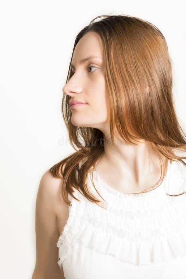 Close up profile of beautiful woaman. Profile of sad beautiful woman in white dress, studio shot on white background royalty free stock photography