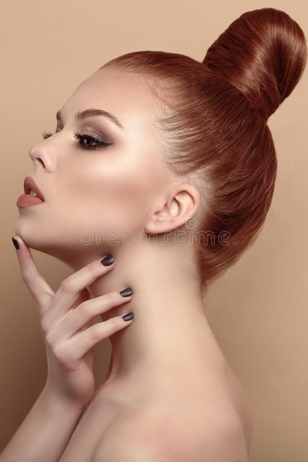 Close up profile portrait of beautiful red-haired model with her hair scraped back into a high bun stock image