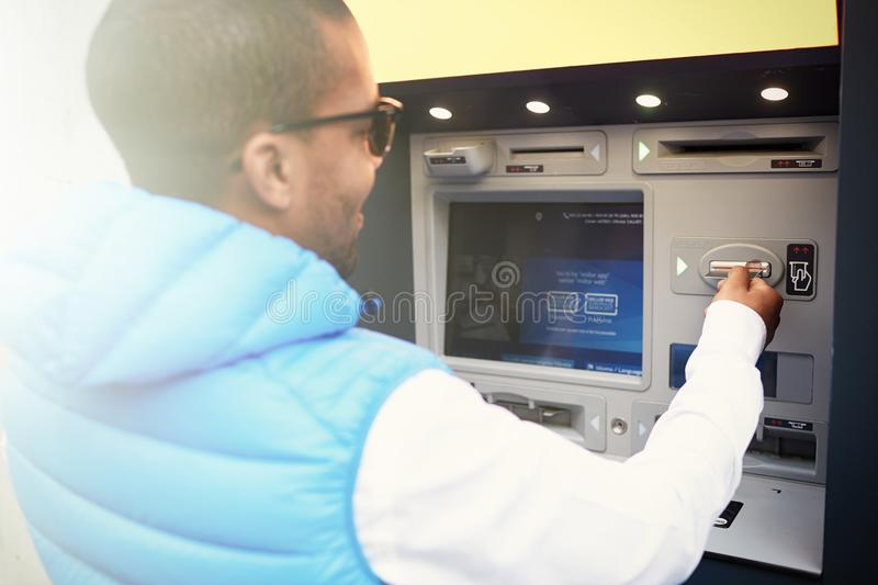Close up profile portrait of black man tourist using ATM machine, following hints in foreign language on its screen stock photos