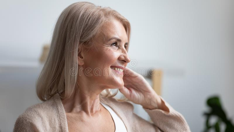 Close up profile smiling mature woman dreaming about good future. Close up profile portrait smiling mature woman dreaming, thinking about good future, beautiful royalty free stock photo