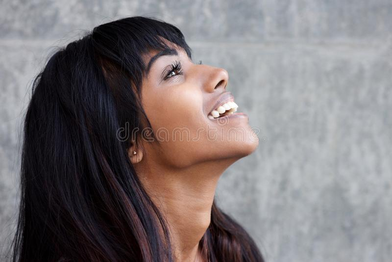 Profile portrait of young Indian woman laughing and looking up royalty free stock image
