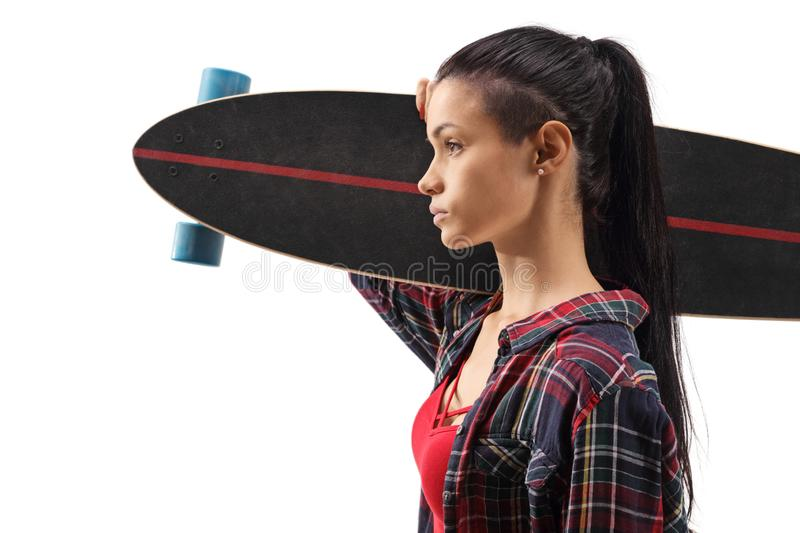Close up profile shot of a young female carrying a longboard on shoulder royalty free stock images
