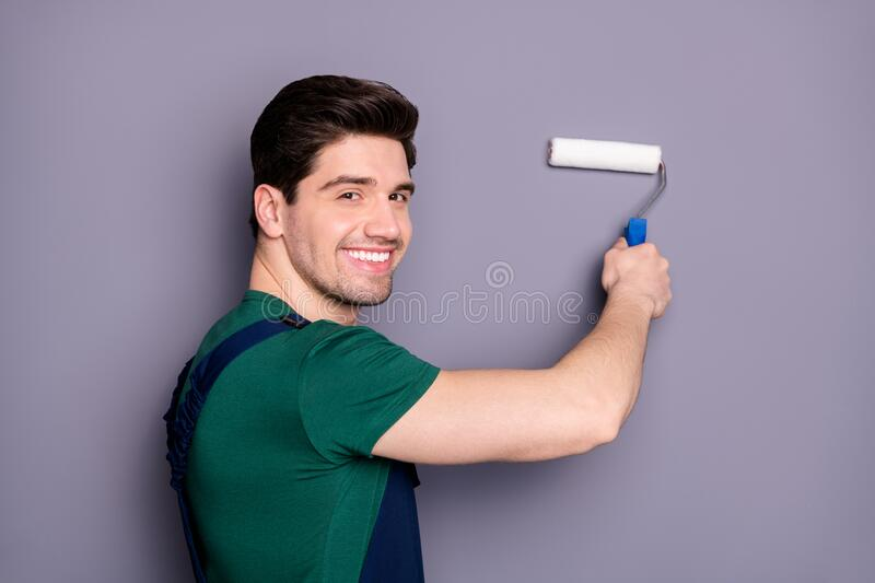 Close-up profile side view portrait of his he nice attractive brunette cheerful cheery guy making renovation restoration. Close-up profile side view portrait of stock photography