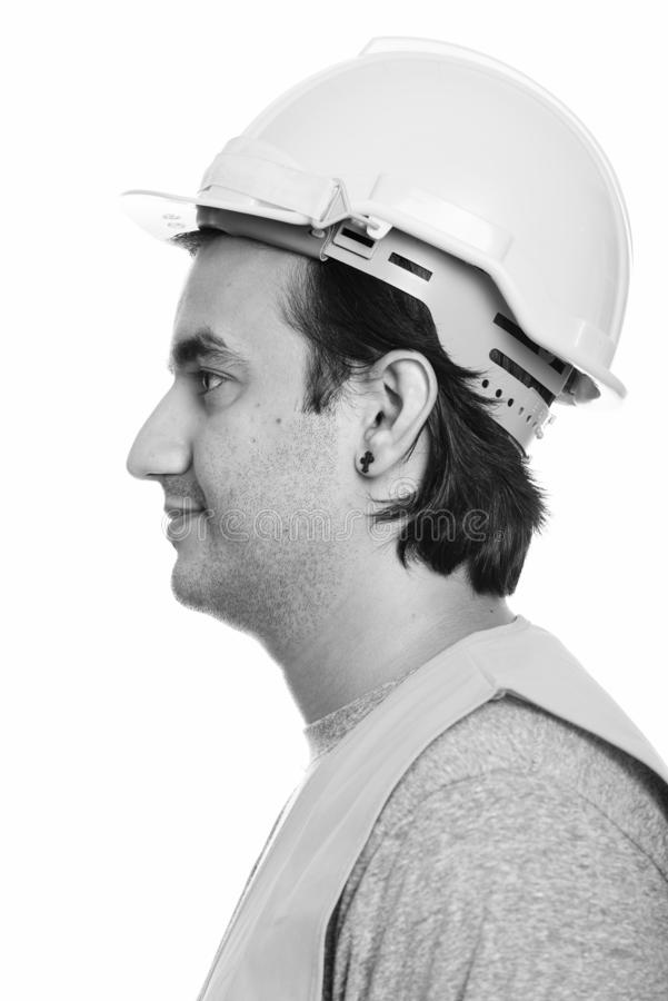 Close up profile view of happy Persian man construction worker smiling. Studio shot of Persian man construction worker isolated against white background in black royalty free stock photos