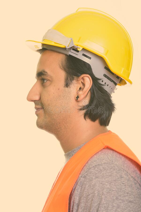 Close up profile view of happy Persian man construction worker smiling stock photo