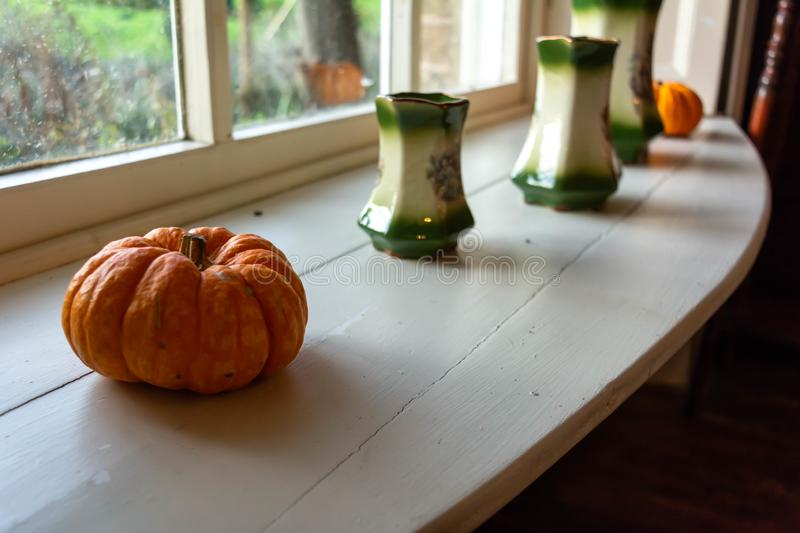 Close Up of Pumpkin and Pots in English Cottage in Countryside in front of Window. On Blurred Background, autumn, decoration, fall, food, fresh, fruit, fun stock image